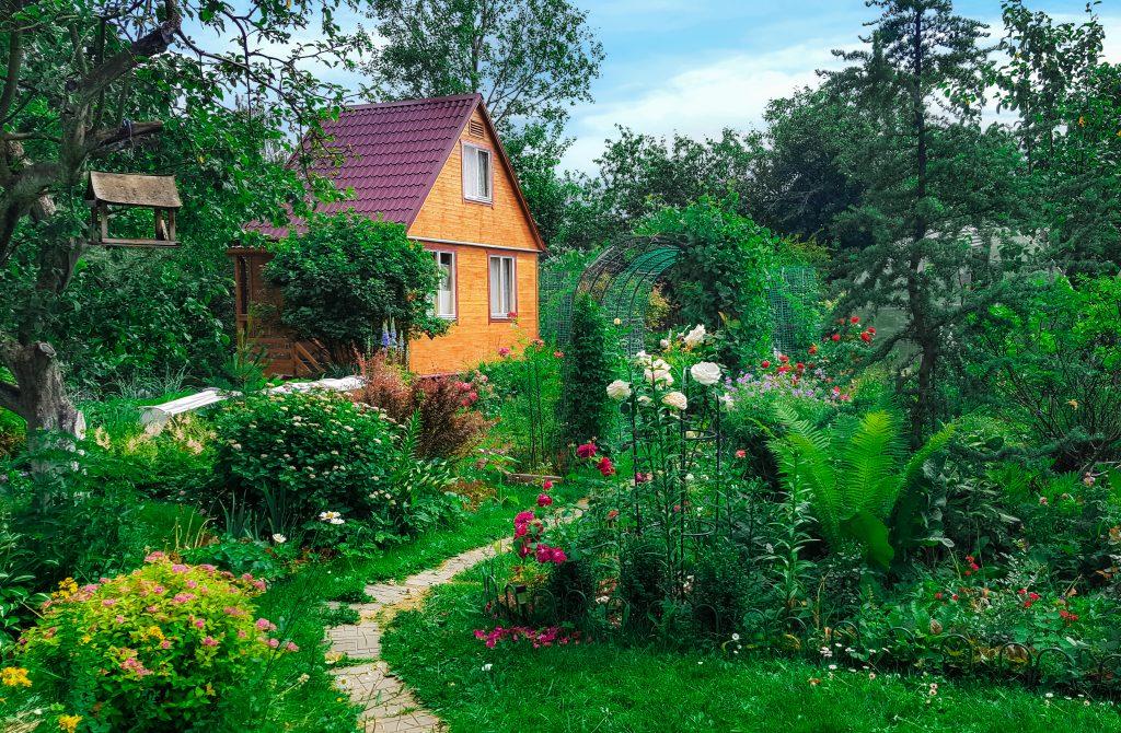 Bespoke Summerhouse created by RG Driveways on background of green garden, landscape.
